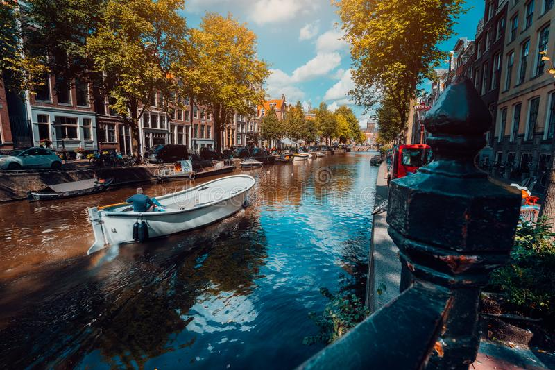 Channel in Amsterdam in autumn sunlight. Boat floating tree-lined canal, vibrant reflections, white clouds in the sky. Netherlands. Houses landmark landscape royalty free stock photo