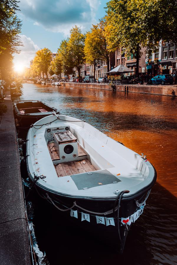 Channel in Amsterdam at autumn sunset. Boat in front of tree-lined canal, white clouds in the sky. Netherlands houses landmark. Landscape. Romantic City trip royalty free stock photography