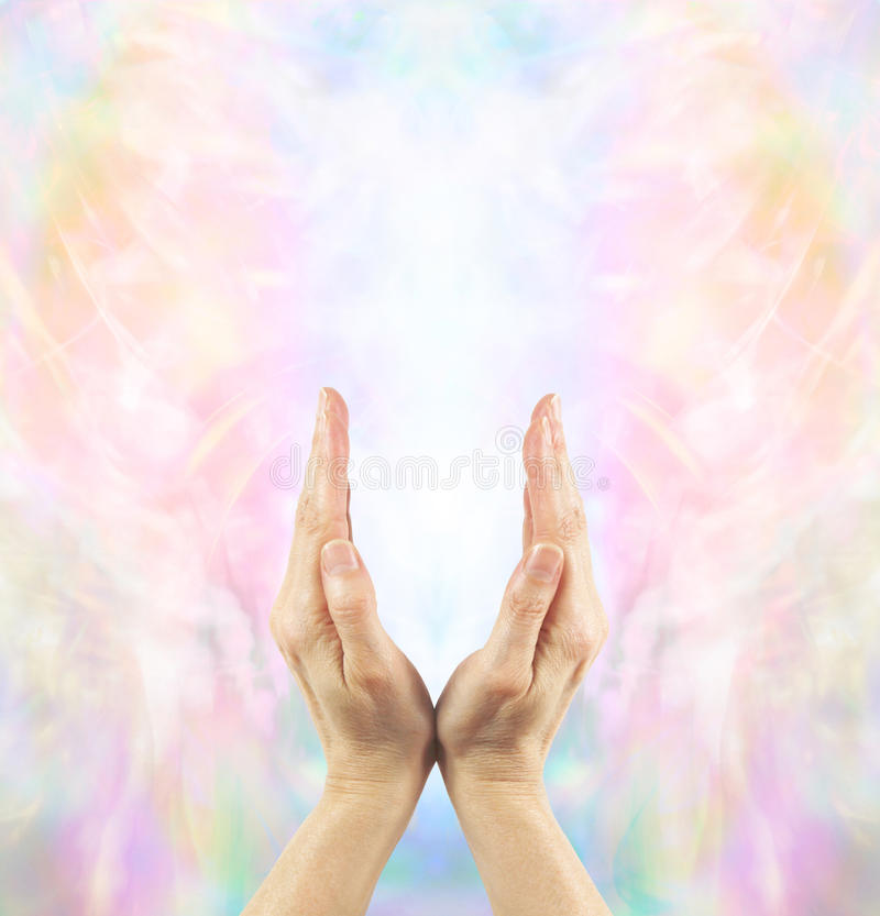Channeling Angelic Healing Energy. Pair of female hands cupped upwards with a beautiful ethereal angelic energy field and white light royalty free stock image