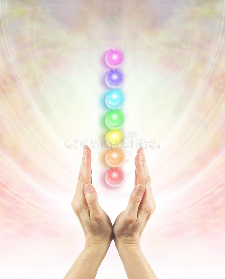 Channeling Chakra Healing Energy. Pair of female hands cupped upwards with a column of seven chakras above on a beautiful ethereal angelic energy field stock photo