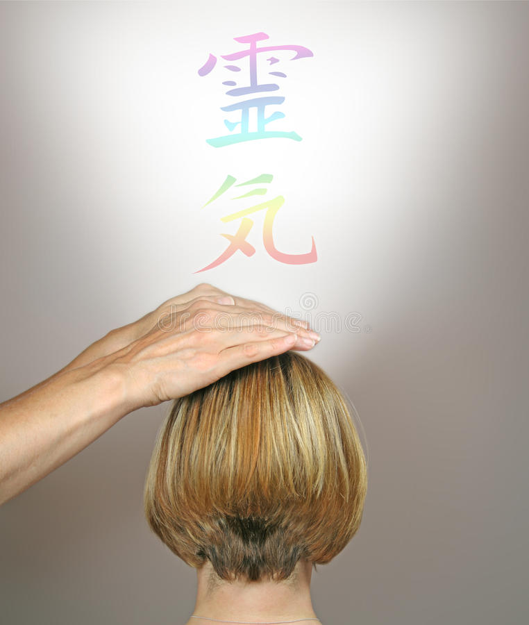 Channeling Healing through Crown Chakra. Female healer channeling healing energy through female client's chakra, with a rainbow colored Reiki Kanji symbol stock images