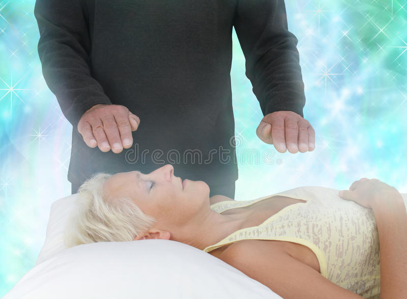 Channeling Healing Energy. Male healer standing over supine female channeling healing through his hands into her aura with a vivid sparkling blue energy royalty free stock images
