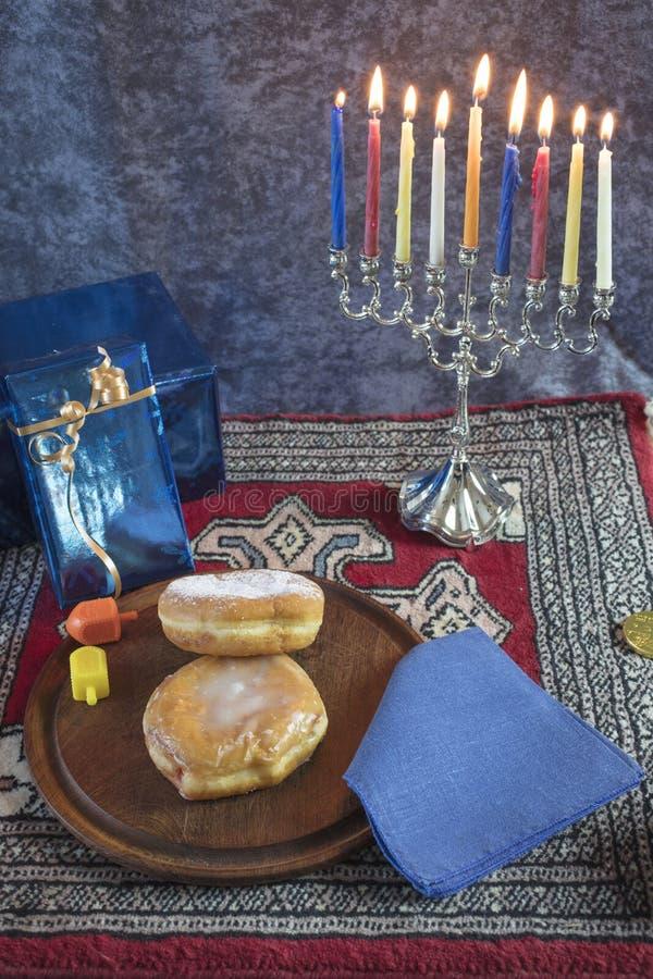 Chanoeka Menorah met aangestoken Kaarsen, Giften, Dreidel en Jelly Fill royalty-vrije stock foto's