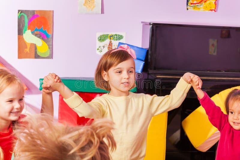 Chanson à refrain de fille avec des enfants dans le jardin d'enfants photo libre de droits