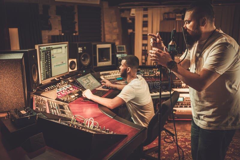 Chanson d'enregistrement d'ingénieur du son et de chanteur dans le studio d'enregistrement de boutique images stock