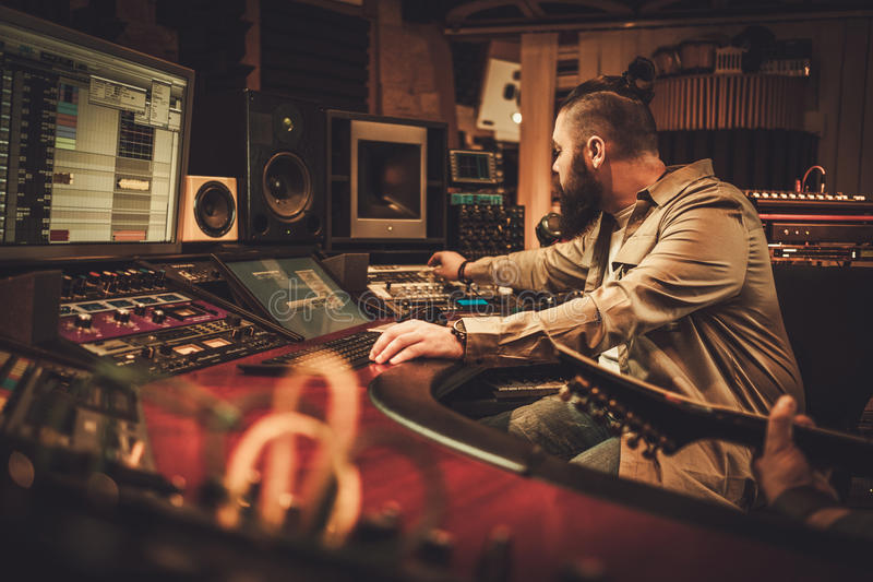 Chanson d'enregistrement d'ingénieur du son et de guitariste dans le studio d'enregistrement de boutique image libre de droits