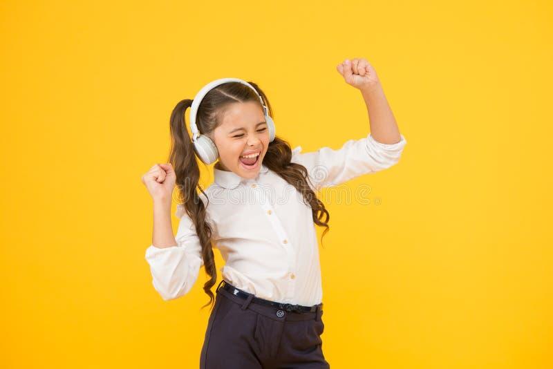 Chanter en musique. Petite enfant mignonne qui suit ses cours de chant sur fond jaune. Adorable petite fille qui la chante image libre de droits