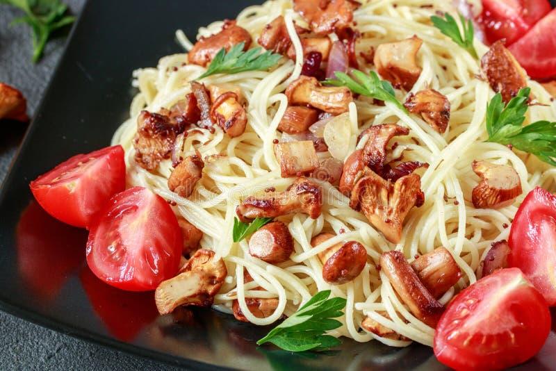 Chanterelle makaron z pieczarkami i pomidorami zdjęcia stock