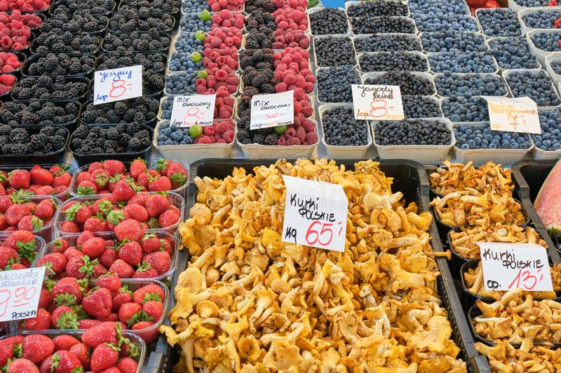 Chanterelles and different kinds of berries. For sale at a market royalty free stock images
