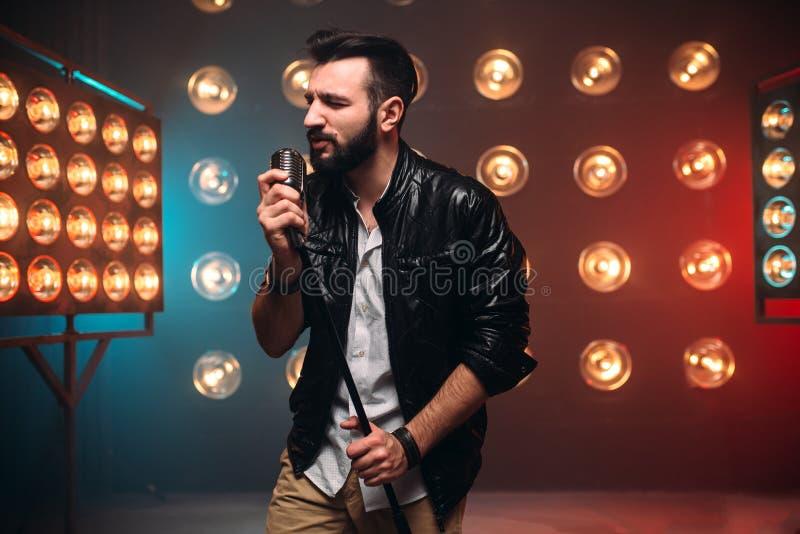 Chanteur barbu brutal avec le microphone sur l'étape photo stock