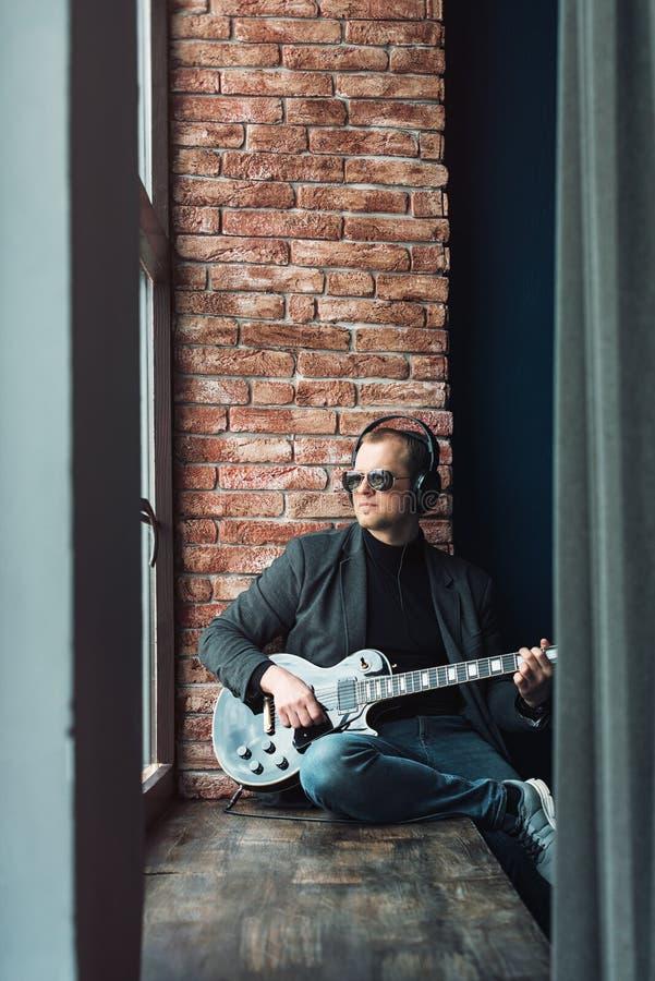 Chanteur d'homme reposant sur un filon-couche de fenêtre dans des écouteurs avec une guitare enregistrant une voie dans un studio photo stock