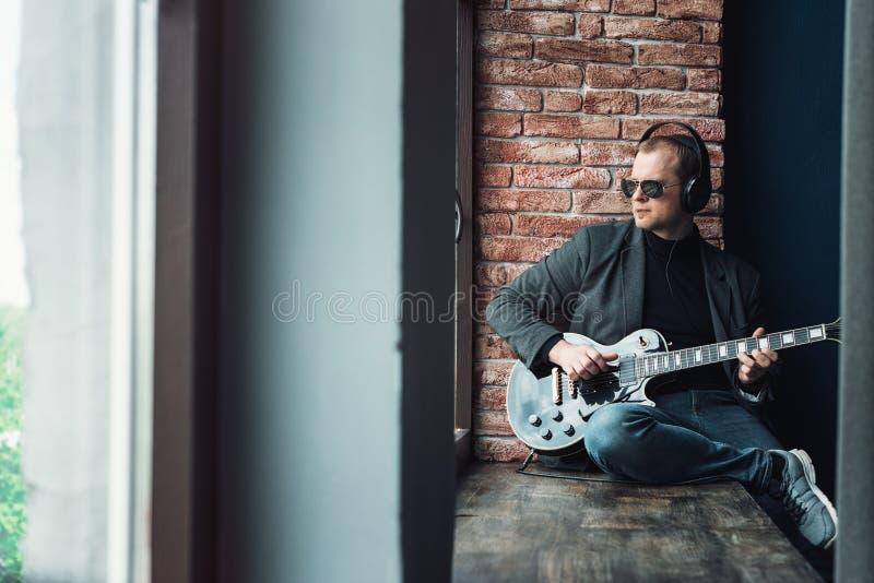 Chanteur d'homme reposant sur un filon-couche de fen?tre dans des ?couteurs avec une guitare enregistrant une voie dans un studio photographie stock libre de droits