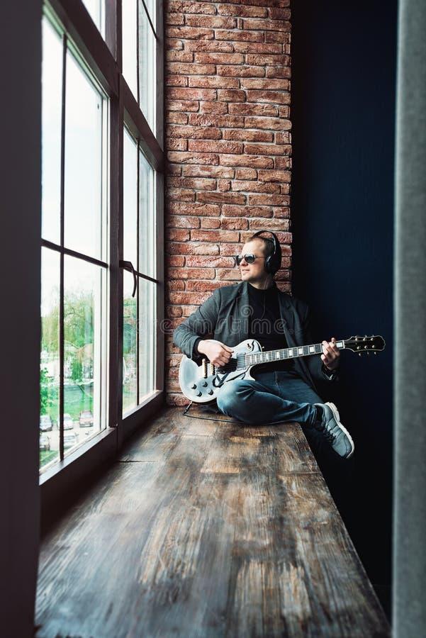 Chanteur d'homme reposant sur un filon-couche de fen?tre dans des ?couteurs avec une guitare enregistrant une voie dans un studio images stock