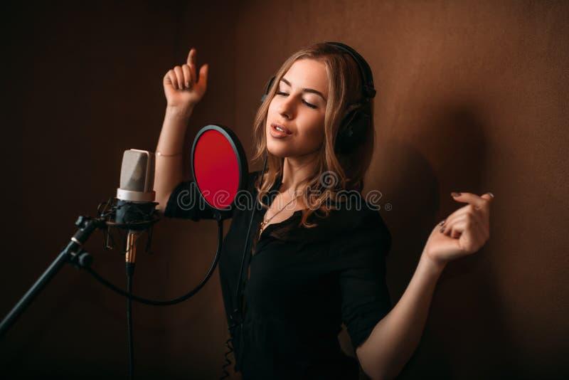 Chanteur de femme dans des écouteurs contre le microphone photographie stock