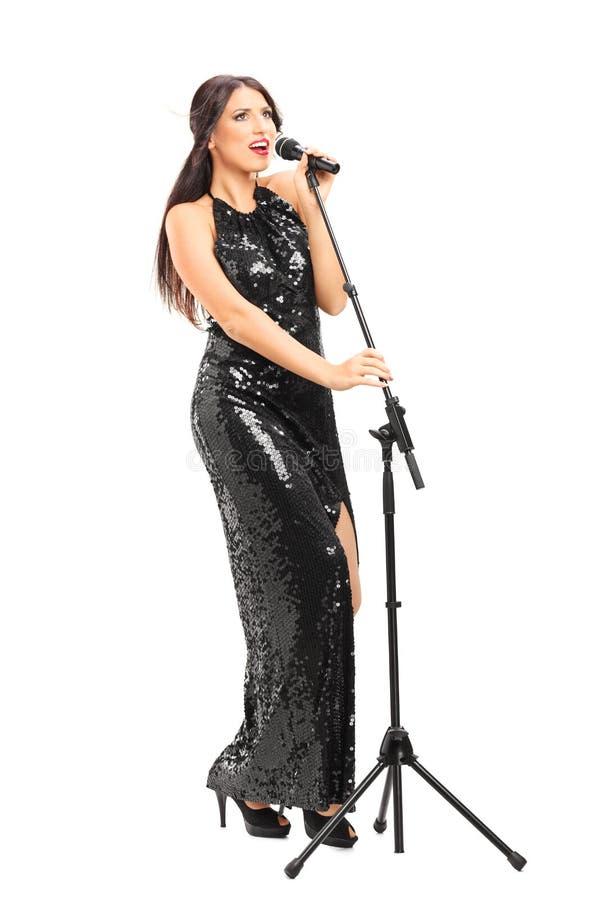 Chanteuse chantant sur un microphone photo stock