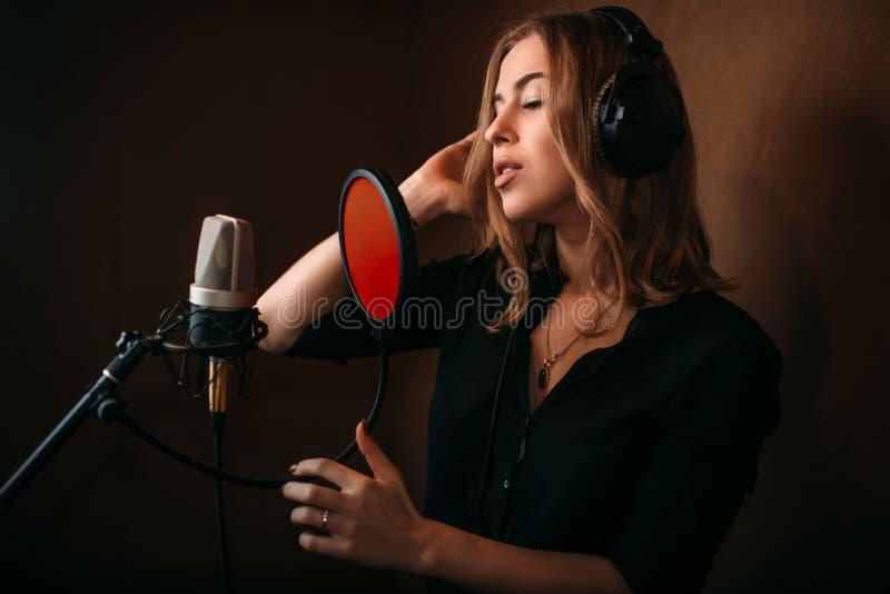 Chanteuse enregistrant une chanson dans le studio de musique photographie stock libre de droits