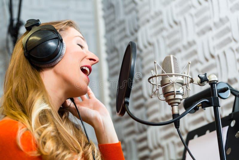 Chanteuse ou musicien pour enregistrer dans le studio images libres de droits