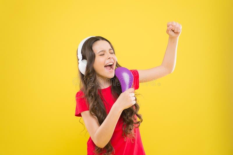 Chantez les textes Les ann?es de l'adolescence d'enfant appr?cient la musique jouant dans des ?couteurs Peu fille appr?ciant la m photographie stock libre de droits