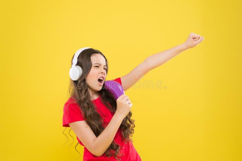 Chantez les textes Peu fille appr?ciant la musique pr?f?r?e Attrapez le rythme ?couteurs de ?coute de musique d'enfant Divertisse photo libre de droits