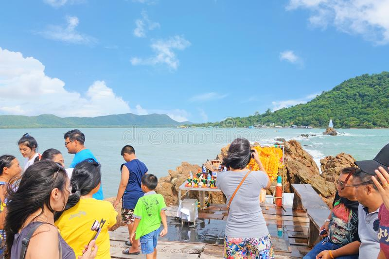 CHANTHABURI THAILAND-26 JULY 2019: travelers on the wooden bridge path to Chedi Hua Laem pagoda on rock in the sea royalty free stock images