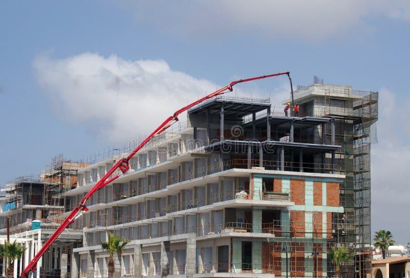 Chantier de construction avec une grande grue télescopique rouge et des travailleurs de bâtiment établissant un grand complexe mo photographie stock