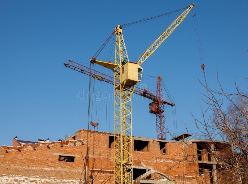 Chantier de construction d'un haut bâtiment de nouvel appartement avec des grues à tour contre le ciel bleu Développement de zone photographie stock libre de droits