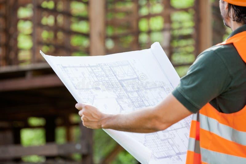 Chantier de construction de Holding Blueprint At d'architecte images stock