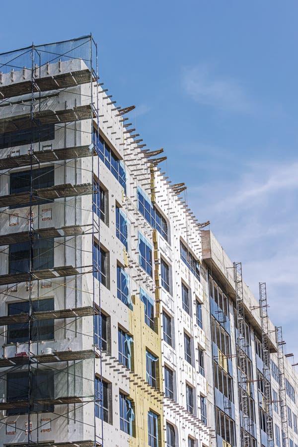 Chantier de construction du bâtiment moderne avec l'échafaudage sur sa façade photos stock