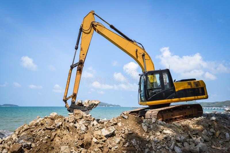 Chantier de construction fonctionnant de pierre défonceuse d'excavatrice de chargeur de pelle rétro sur l'océan de mer de plage image stock