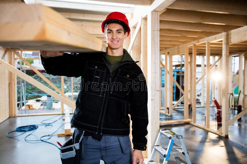 Chantier de construction masculin de sourire de Carrying Wood At de charpentier photographie stock