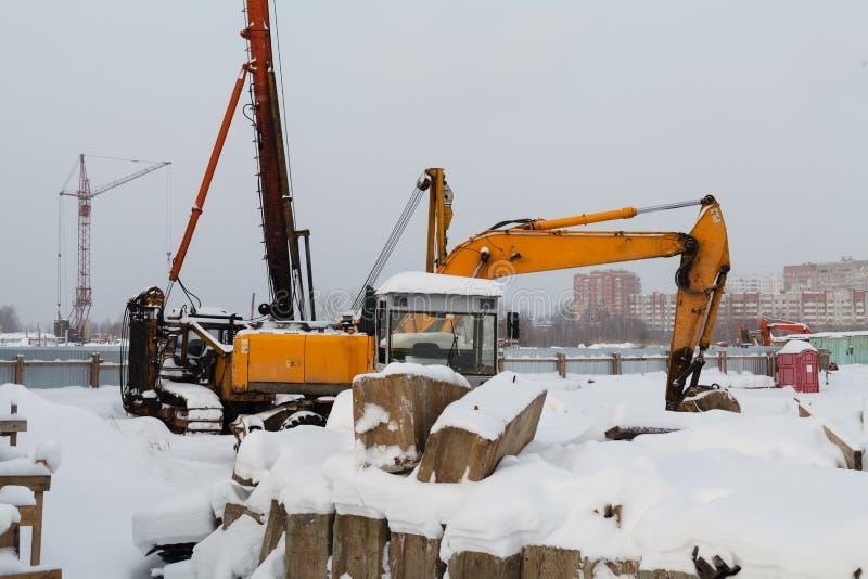 Chantier de construction pour la pose de nouveaux canaux et tuyaux devant un grand, laid immeuble avec un bon nombre de bon march photo libre de droits