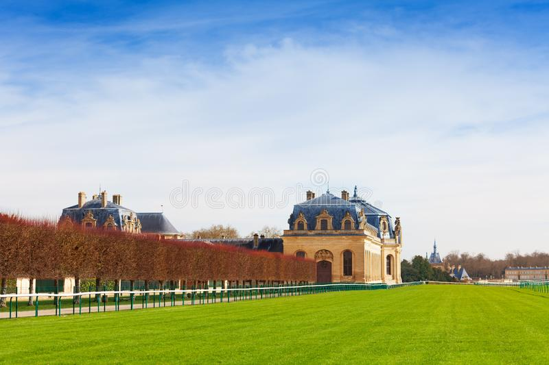 Chantilly racecourse of the Great Stables, France. Chantilly racecourse and Great Stables building at sunny day, France stock image