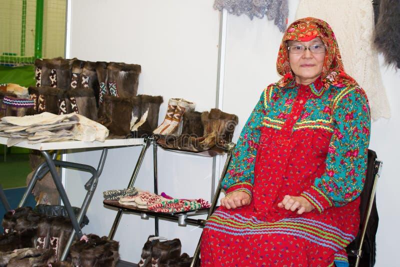 CHANTY-MANSIJSK, RUSSIA 17 febbraio 2017 Donna in costume nazionale della gente ugro-finnica in Khanty vicino alle scarpe naziona fotografia stock libera da diritti