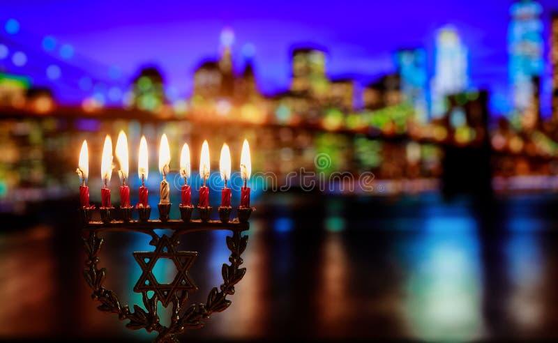 Hanukkah menorah symbol of Jewish traditional holiday Brooklyn Bridge over night New York City with lights stock photography