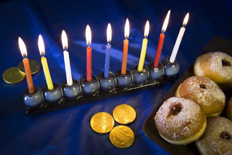 Chanukka-Tabelle mit Schaumgummiringen und Kerzen lizenzfreie stockfotos