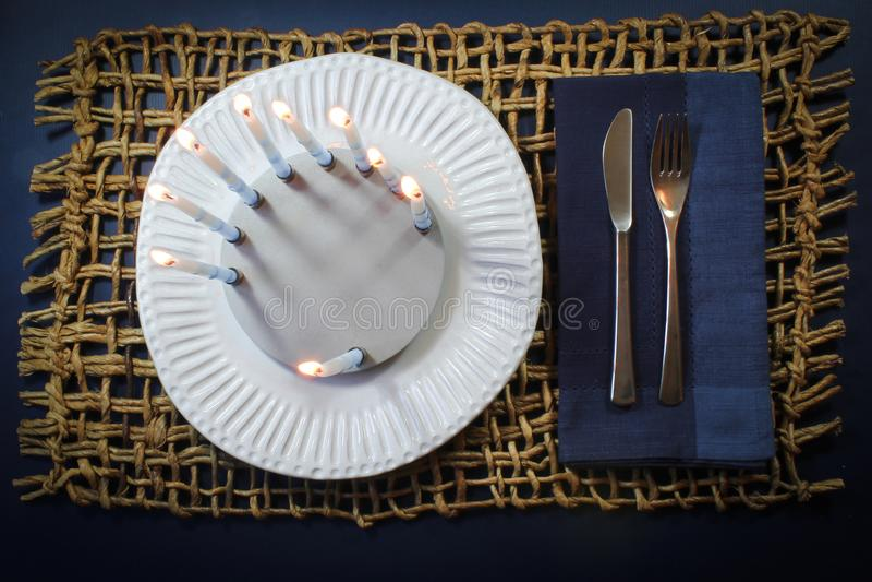 Chanukkahbakgrund med runda menoror på en vit matställeplatta med den blåa servetten och lantligt vävt mattt royaltyfria foton