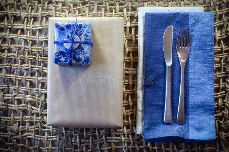 Chanukkahgåvor på en lantlig vävd placemat med den blått servetten och bestick royaltyfria foton