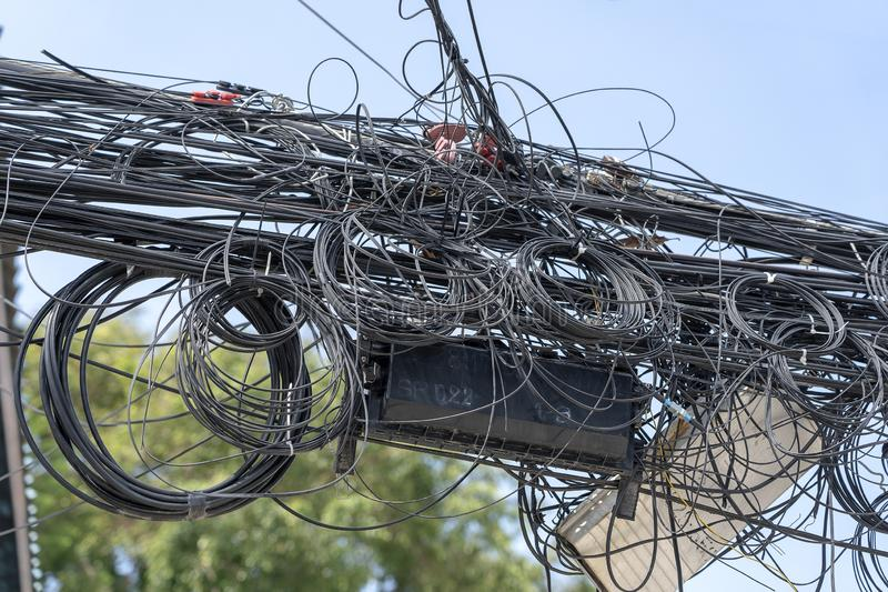 Chaos of cables and wires on an electric pole. Many electrical cable - wire and telephone line on electricity post, Thailand. Wire and cable clutter. Potential stock photos