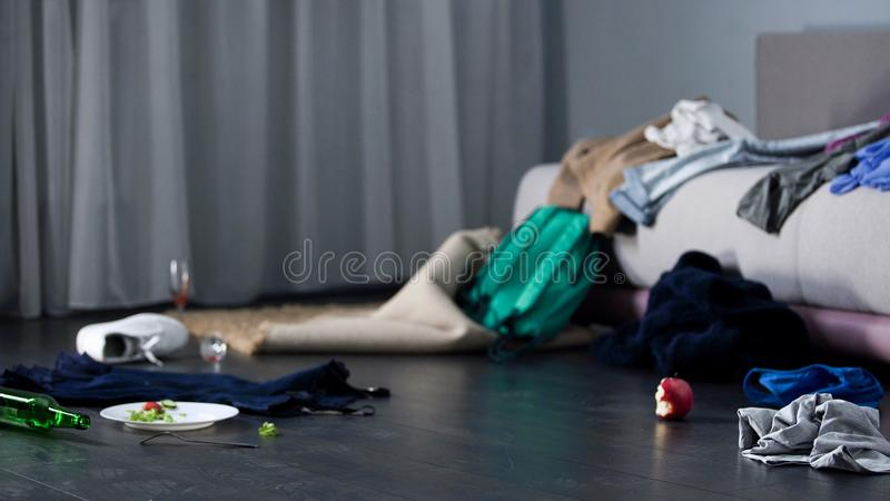 Chaos and mess in room after party, cloth and food on floor, bachelor apartment. Stock footage stock photos