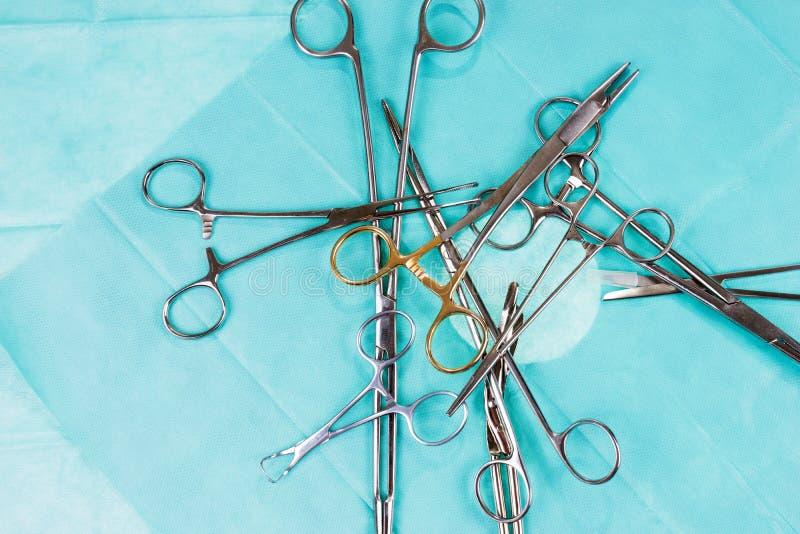 Chaos op de werkende lijst Chirurgische schaar en klemmen op groen gaas stock afbeeldingen