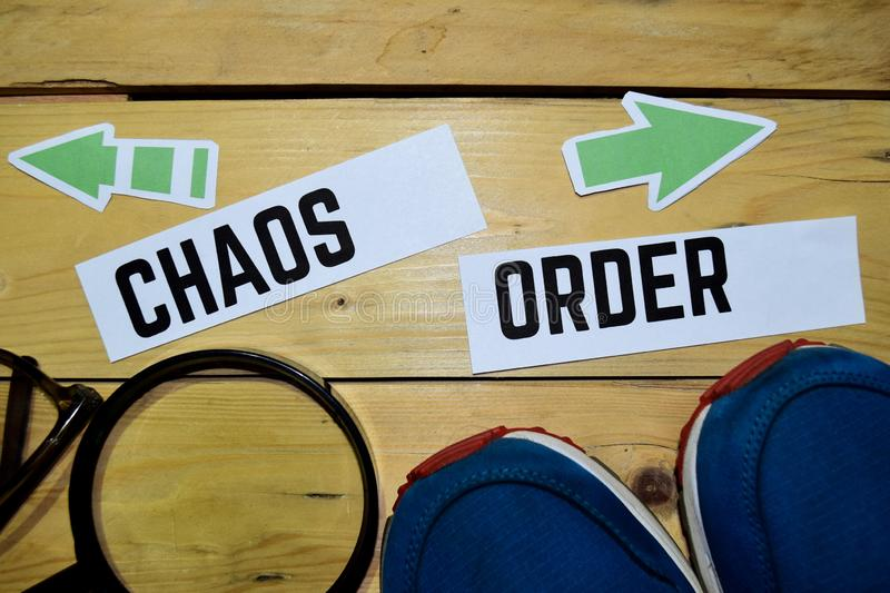 Chaos or Order opposite direction signs with sneakers,magnifying and eyeglasses on wooden. Vintage background. Business and education concepts royalty free stock image
