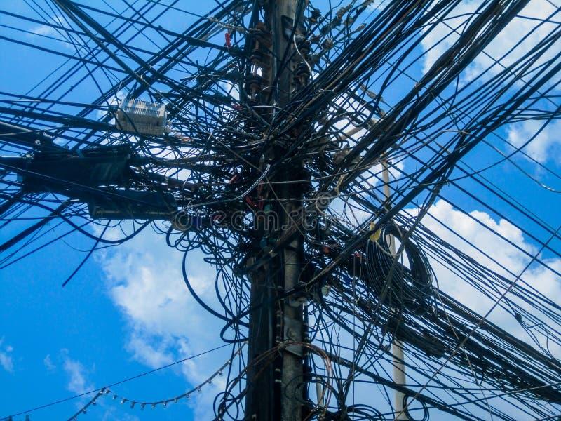 Chaos von Kabeln und von Drähten auf einem elektrischen Pfosten, Thailand Draht- und Kabelunordnung stockfoto