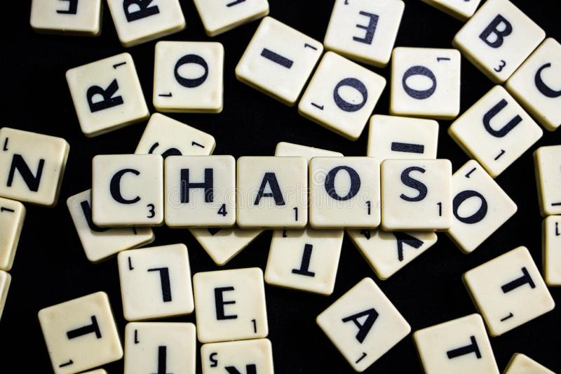 Chaos word spelled with scrabble letters in black background royalty free stock images