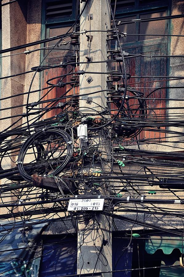 Chaotic electric power transmission. Many chaotic cables connected to the pole for power transmission stock photos