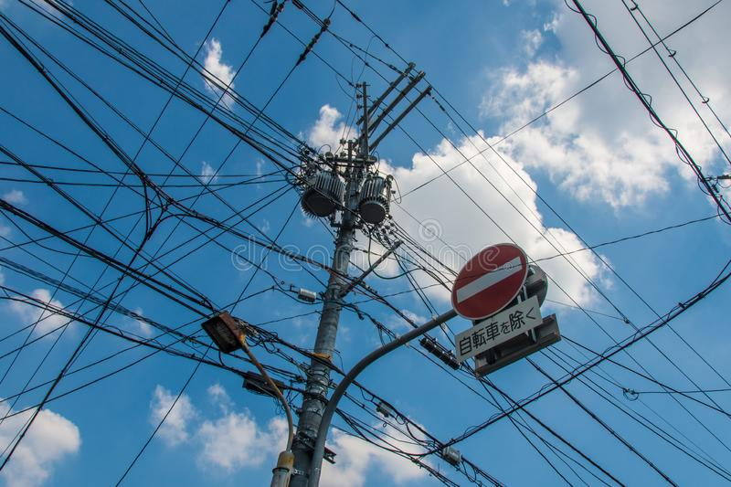 Chaotic messy electric and telephone mast in kyoto. One way sign stock image