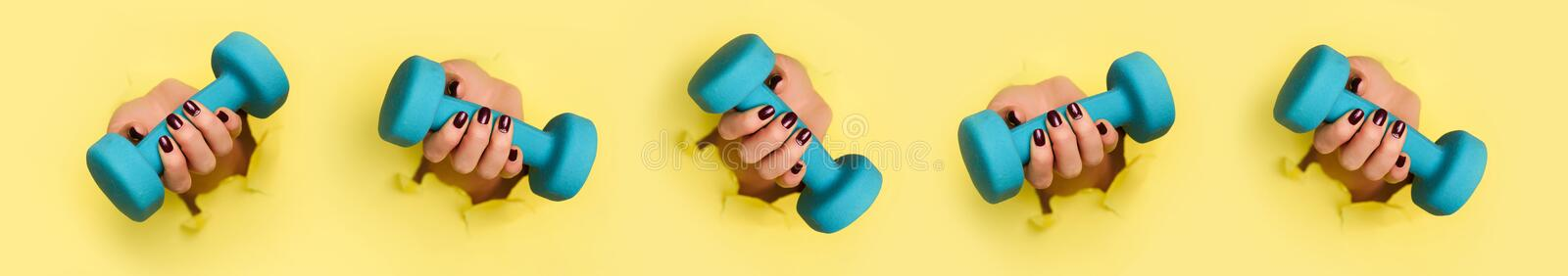 Chaotic pattern of female woman hand holding blue dumbbell on yellow background. Fitness, sport, healthy lifestyle, diet concept. stock photography