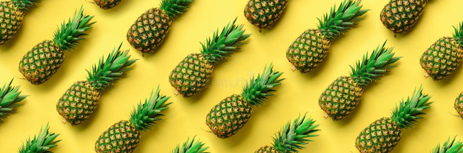 Chaotic pineapple pattern for minimal style. Top View. Pop art design, creative concept. Copy Space. Banner. Fresh. Pineapples on yellow background stock image