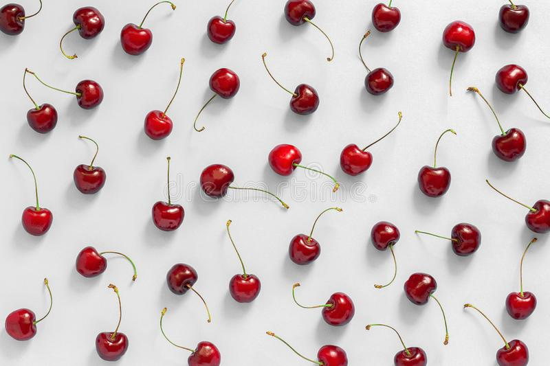 chaotically scattered red ripe sweet cherry on grey background, texture Top view, Flat lay royalty free stock photos