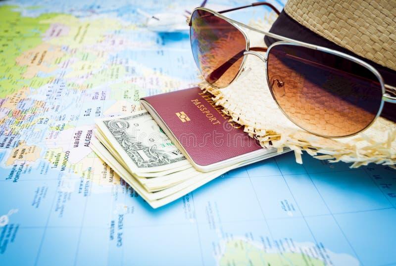 Chapéu, óculos de sol, passaporte, dinheiro e aviões no mapa do mundo foto de stock