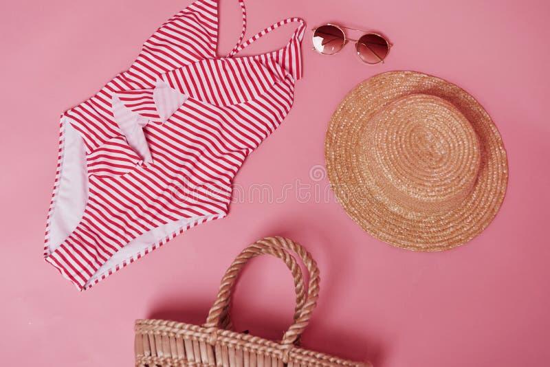 Chapéu, óculos e saco Bikini na mesa cor-de-rosa Grupo de objetos para viagens e férias imagem de stock royalty free